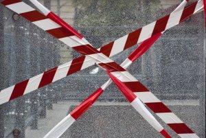 Červeno-biela bezpečnostná páska pred rozbitým sklom
